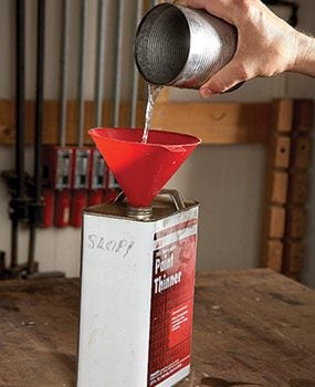 Pouring used solvent into a slop can.