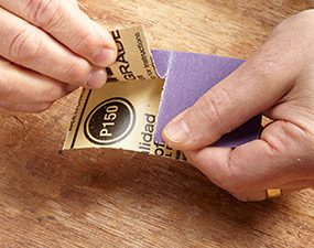 Folding sandpaper to make a sandpaper pad.