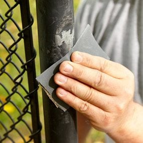Lightly scuff and sand the vinyl coated chain-link fence post.