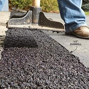 Add additional layers of cold patch to fix the sunken area of driveway.
