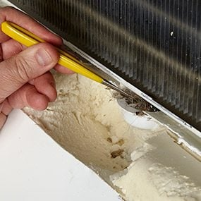 Remove the debris that's causing the leaking refrigerator.