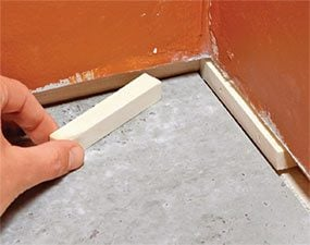 Many finish carpenters use spacer blocks to stop the baseboard from tilting in.