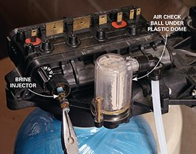 Install the new injector for the water softener control head.