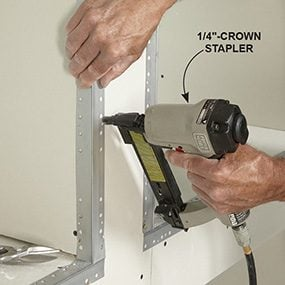 Use a stapler to attach the corner beads for the built-in bookcase.
