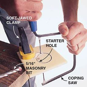 Cutting a hole in ceramic tile with a coping saw.