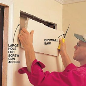 Cutting a hole in a wall when repairing a pocket door.