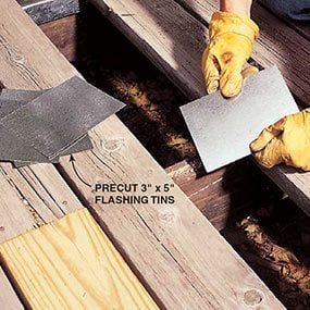 Installing flashing on decaying joists when replacing deck boards.