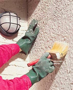 Applying whitewash to a stucco wall.