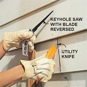 Cutting out rotted siding with a utility knife when replacing siding.