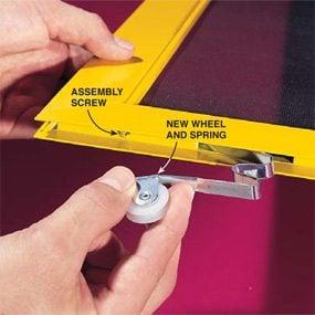 Installing a new wheel into a sliding screen door.
