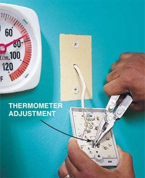 Adjusting a thermostat's thermometer.