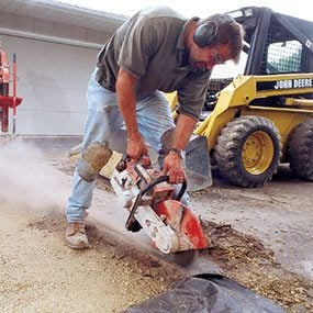 Cutting a concrete slab with a gas-powered saw.