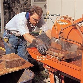 Cutting tile with a wet-cutting masonry saw.