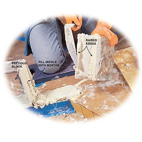 Buttering blocks with mortar is a key skill in learning how to install a glass block shower.