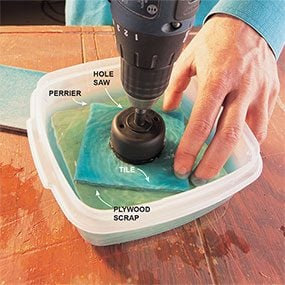 Immersing tile in a shallow pool of water to prevent heat shock when drilling into ceramic tile.