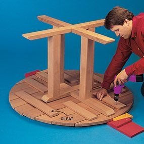 Finish building the picnic table by attaching the base to the top.