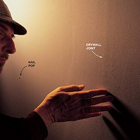 Highlighting imperfections in a wall by shining a bright light on it when finding studs in a wall.
