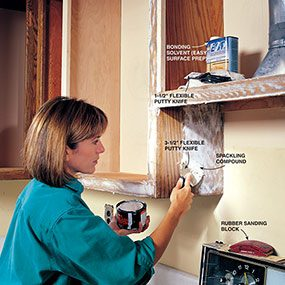 Filling holes and wood grain with spackle is part of refinishing a kitchen cabinet.