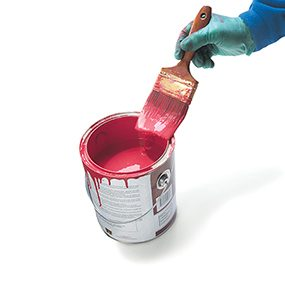 Scraping off excess paint when cleaning a paint brush.