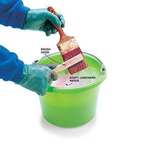 Using a brush comb and a pail of soapy water to clean a paint brush.