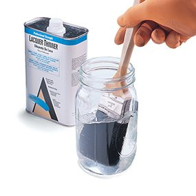 Dipping a paint brush in lacquer thinner when cleaning a paint brush.