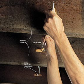 Pull new cable through holes in the joists to power the floor outlet.