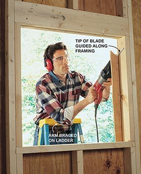 Using a reciprocating saw to cut plywood from a window hole when sheathing a house during framing.