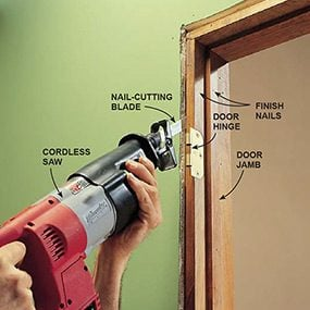 Using a reciprocating saw to cut the nails anchoring a door jamb to the rough opening.