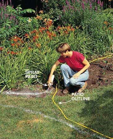 <b>Photo 1: Mark the patio outline</b></br> Outline the patio with a garden hose. Then mark 6 in. beyond the perimeter with spray marking paint. Also align adjoining paths.
