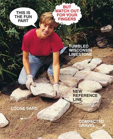 <b>Photo 8: Set the border stones</b></br> Establish the patio height with strings stretched across the edges of the patio. Set the strings parallel to the gravel base and at a height equal to the thickness of a brick (not a stone) plus a 1-in. sand bed plus an extra inch for clearance. Spread a layer of sand. Set a perimeter stone onto the sand bed and wiggle it down into the sand until it's sitting 1 in. below the string. Add sand to raise the height of the stone if necessary. Continue adding stones, assembling them like a jigsaw puzzle.