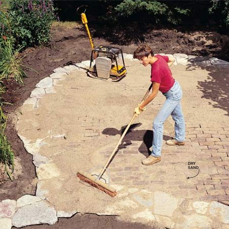 <b>Photo 18: Sweep sand into the joints</b></br> Spread dry sand over the stones and bricks and work it down into the cracks with a broom. Tamp with the plate compactor. Keep spreading sand and tamping until the joints are full.