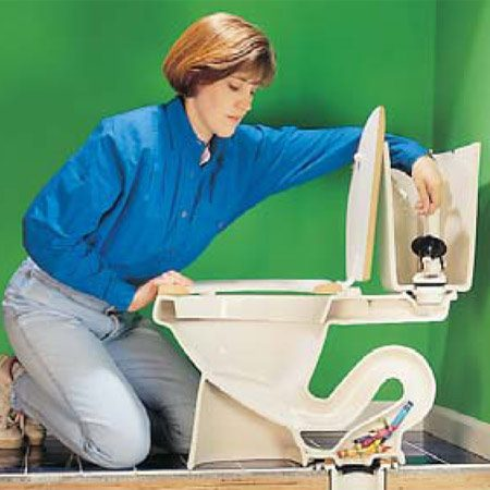 <b>Photo 2: Test for a clog</b></br> Don't flush the toilet if you suspect that it's clogged. Instead, remove the tank lid and lift the flapper valve slightly to let a cup or two of water into the bowl to see if the water goes down. Flushing a clogged toilet may flood your floor!