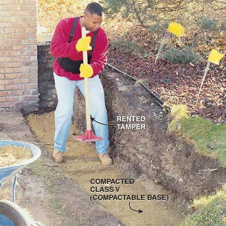 <b>Photo 2: Compact a gravel base</b></br> Install 4 to 6 in. of base material level to the tops of the stakes, then compact it until it's about 1 in. below the tops. Rent a hand tamper for small projects, or a gas powered tamper for walls more than 30 ft. long.