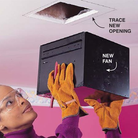 <b>Photo 4: Fit the new fan housing</b></br> Trace the new fan housing outline on the ceiling over the old opening. Enlarge the hole with a drywall saw. Pay attention to ceiling joist locations.