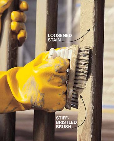 <b>Photo 4: Scour the railing</b></br> Scrub loosened finish off the surface with a synthetic stiff-bristle brush. It'll take some muscle to pull the finish loose from the wood.