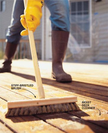 <b>Photo 7: Scrub the deck</b></br> Scrub away the loose wood fibers and residue 15 minutes after you've applied the cleaner. Work the brush deeply into the wood in the direction of the grain. As soon as you're finished, rinse the deck thoroughly with a firm spray from your garden hose and let the surface dry for at least two days.