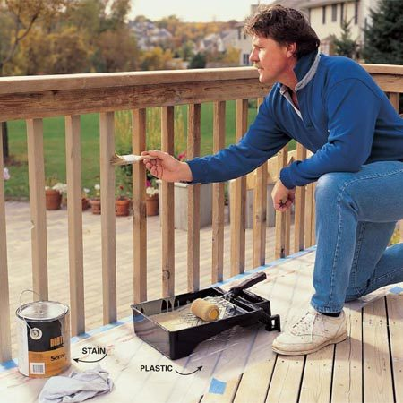 <b>Photo 8: Stain the railing</b></br> Brush your stain onto the railings. Cover your deck boards with tape and plastic to catch the drips. We recommend a semitransparent oil stain. Solid color stains have heavy pigment that'll be tough to renew the next time you refinish the deck.
