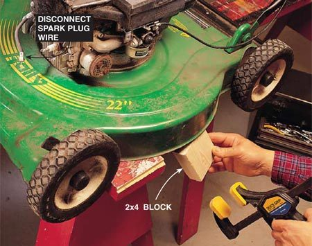 <b>Photo 1: Block the blade</b></br> Remove the spark plug wire. Then clamp a 2x4 block to the shroud to keep the blade from turning as you remove it.