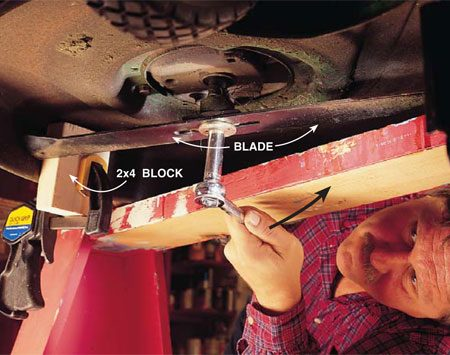 <b>Photo 2: Remove the blade</b><br/>Squirt penetrating oil on the bolt head that holds the blade to the engine shaft. Give the oil 15 minutes to work its way into the threads. Using a socket wrench, turn the nut in the same direction you would to remove a lid from a mayonnaise jar. Mark the blade on the bottom so you can install it properly again.