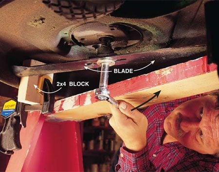 <b>Photo 2: Remove the blade</b></br> Squirt penetrating oil on the bolt head that holds the blade to the engine shaft. Give the oil 15 minutes to work its way into the threads. Using a socket wrench, turn the nut in the same direction you would to remove a lid from a mayonnaise jar. Mark the blade on the bottom so you can install it properly again.