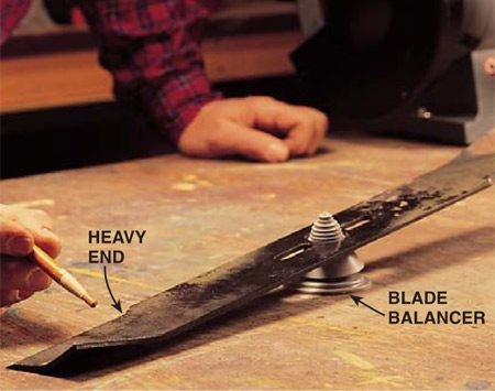 <b>Photo 6: Check the blade's balance</b></br> Balance the blade with a special plastic balancer available at hardware stores. Mark the heavy end and grind steel from the very end of the blade (not the cutting edge) to reduce the weight.