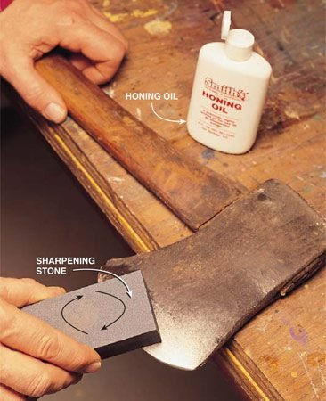 <b>Photo 9: Use a sharpening stone on the ax</b></br> Grind the filed edge with a sharpening stone. Squirt a generous amount of honing oil on the stone and use a swirling circular motion into the blade. Keep the bevel the same as before. Use the coarse side of the stone first, then the fine. Keep lubricating the stone with oil (use water for a special water stone) for a clean edge.