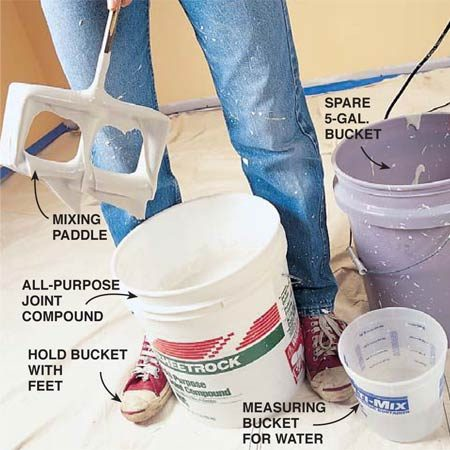 <b>Photo 2: Add water to the joint compound and mix it </b><br/><strong>Thin</strong> the joint compound, or &ldquo;mud,&rdquo; with water. Use a blade mixer mounted to a variable-speed 1/2-in. drill (most mixers are too large for 3/8-in. drills). You can also mix the mud by hand with a 5-gal. paint stirring stick (available free at paint stores). Scoop half of a full bucket of unthinned mud into an empty 5-gal. bucket and add the correct amount of water to both buckets. Hug the bucket firmly with your feet and stir. After the initial stirring, scrape the sides and bottom with a stick or your hand and stir again. The second stirring helps remove thicker clumps that can clog the spray gun.