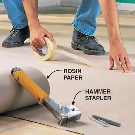 <b>Photo 5: Tack down rosin paper</b></br> Sweep or vacuum the floor clean. Tack down rosin paper (available at any home center or flooring supplier) with a stapler. Lap the joints 6 in. and tape the seams with 2-1/2 in. masking tape.