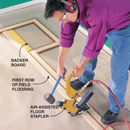 <b>Photo 11: Nail the first row</b></br> Install the first row of field flooring with a floor nailer. (Another 1x4 backer board is screwed in place temporarily to bridge gaps in the border.) Nail (or staple) with 2-in. fasteners every 6 in. To prevent splitting, keep fasteners 4 in. away from the ends of boards.