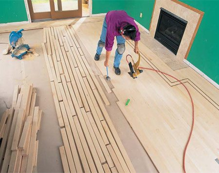 <b>Photo 18: Lay out and nail the field</b></br> Lay out the field flooring by staging several feet of flooring ahead of installation. Stagger all end joints at least 6 in. Before fastening, tap the flooring into place with the floor nailer mallet. Work inward from each side.