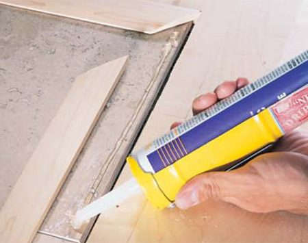 <b>Photo 20: Install transitions</b></br> Glue down reducer strips with silicone caulk on hard surfaces such as tile.