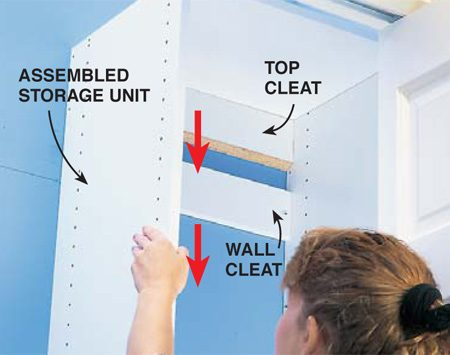 <b>Photo 5: Hang the cabinet</b></br> Hang the assembled storage unit by pushing it tight to the wall and sliding it down onto the interlocking cleat.