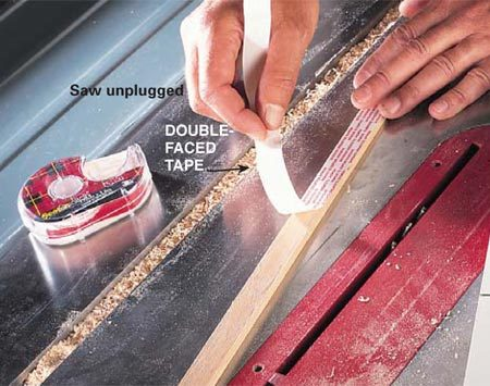 <b>Photo 4: Position and mount the right runner</b></br> <p>Sprinkle sawdust in the right slot, press double-faced tape onto the second runner and lay it tape side up into the slot (the sawdust shims the runner above the table surface so the tape will stick to the sled bottom). The strip should be flush with the infeed edge of the saw table. Align the sled table with the infeed edge of the saw table, then lower the fixed left runner into the slot and lower the right side of the sled onto the taped runner. Carefully lift the sled off the saw, then screw on the second runner.</p>