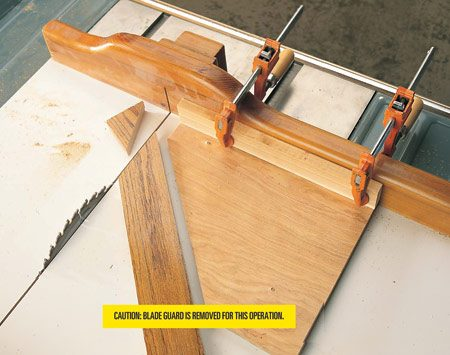 <b>Photo 15: Miter with the jig</b></br> <p>Clamp the miter jig to the sled fence with 2 in. of the jig tip projecting past the right side of the saw path, then cut off the tip. This gives you room to move wood back and forth to fine-tune lengths. Grip cutting stock firmly against the jig and use it as a guide for cutting 45-degree angles.</p> <p><strong>Caution:</strong> Blade guard is removed for this operation.</p>